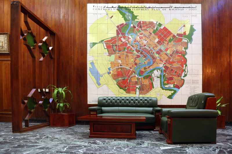 Photograph by Ahmad Mousa, 2018. Room with green sofas, wooden table, wooden walls and a large development plan map of Baghdad.